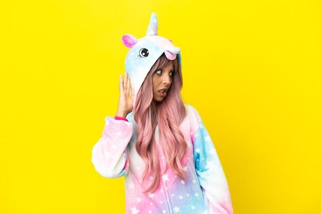 Joven mujer de raza mixta vistiendo un pijama de unicornio aislado sobre fondo blanco escuchando algo poniendo la mano en la oreja