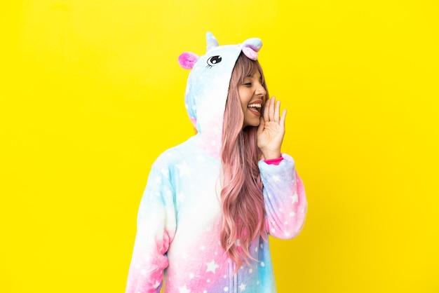 Joven mujer de raza mixta vistiendo un pijama de unicornio aislado sobre fondo blanco gritando con la boca abierta hacia el lateral
