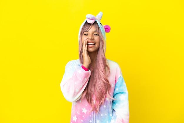 Joven mujer de raza mixta vistiendo un pijama de unicornio aislado sobre fondo blanco gritando con la boca abierta