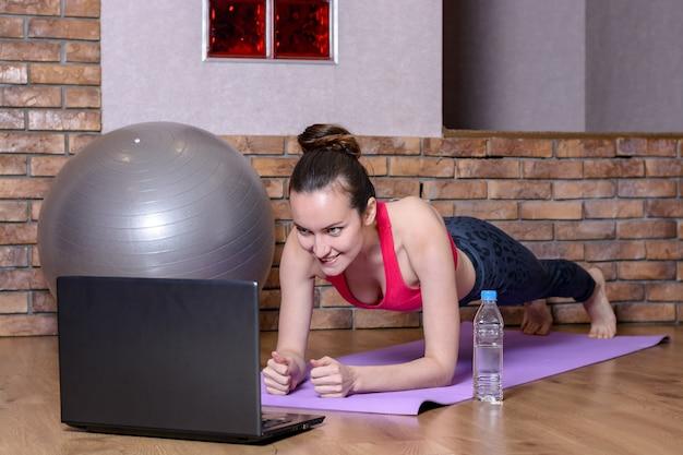 Una joven mujer realiza un ejercicio de tabla sobre una estera púrpura en el piso de parquet y mira videos instructivos en la computadora portátil