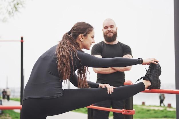 Joven y mujer realizan ejercicios y estrías antes de hacer deporte