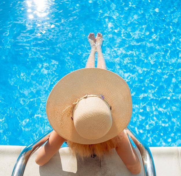 Una joven mujer se relaja en la piscina