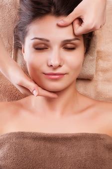 La joven mujer relajada disfruta de recibir un masaje facial en el salón del spa