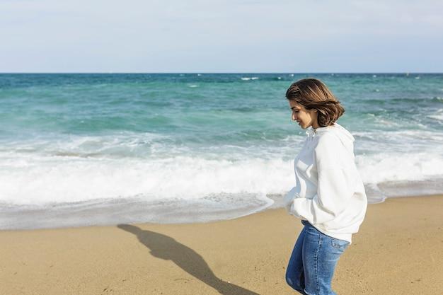 Joven mujer relajada disfrutando y caminando solo en la playa