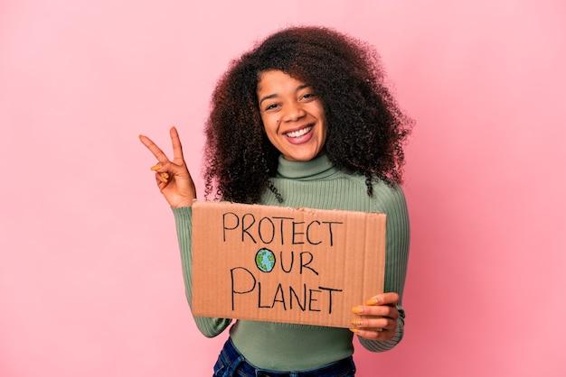Joven mujer rizada afroamericana alegre y despreocupada mostrando un símbolo de paz con los dedos.