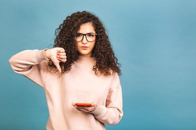 Joven mujer rizada enviando mensajes de texto con smartphone sobre fondo azul aislado con cara enojada