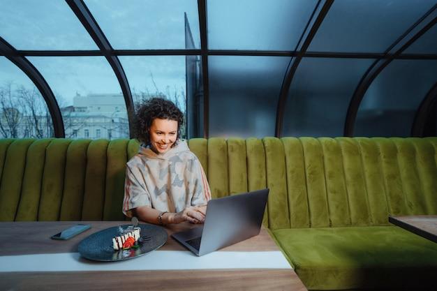 Joven mujer rizada sonriente usando la computadora portátil en la cafetería con espacio de copia