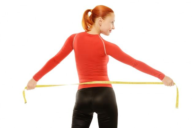 Joven mujer roja con cinta métrica