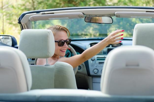 Joven mujer roja saludando a sus amigos mientras conduce