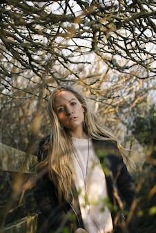 Joven mujer rubia con un abrigo negro de pie sobre un camino rodeado de árboles sin hojas