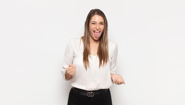 Joven mujer rubia con actitud alegre, despreocupada y rebelde, bromeando y sacando la lengua, divirtiéndose