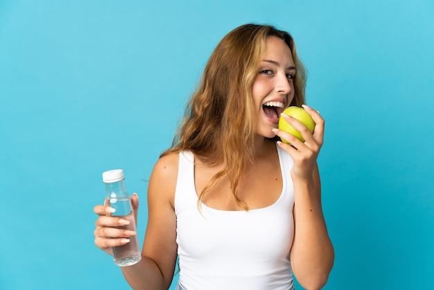Joven mujer rubia aislada en la pared azul con una botella de agua y comiendo una manzana