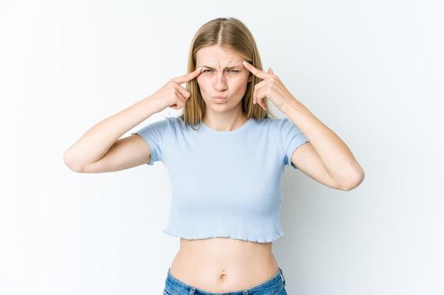 Joven mujer rubia aislada en la pared blanca se centró en una tarea, manteniendo los dedos índice apuntando la cabeza