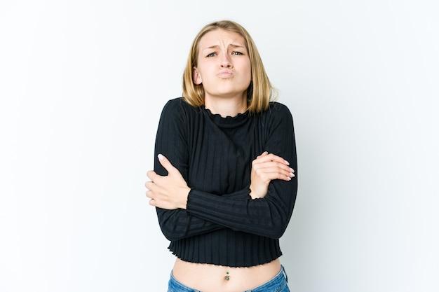 Joven mujer rubia aislada en la pared blanca sopla las mejillas, tiene expresión cansada