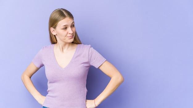 Joven mujer rubia aislada en la pared púrpura soñando con lograr metas y propósitos