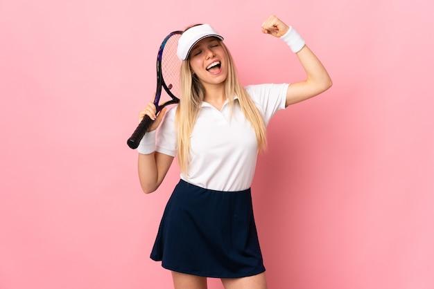 Joven mujer rubia aislada en la pared rosa jugando al tenis y celebrando una victoria
