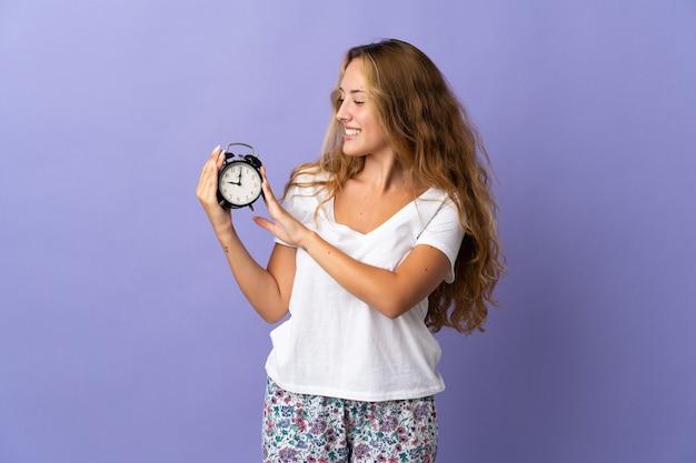 Joven mujer rubia aislada en púrpura en pijama y sosteniendo el reloj con expresión feliz