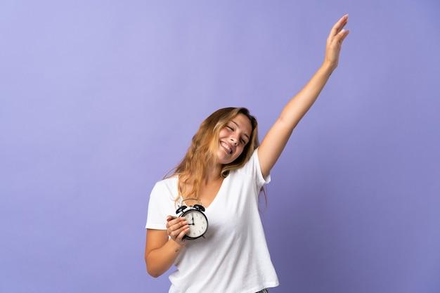 Joven mujer rubia aislada en púrpura en pijama y sosteniendo el reloj haciendo gesto de victoria