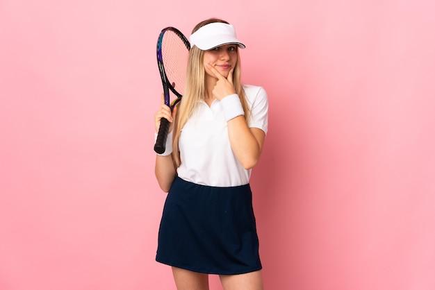 Joven mujer rubia aislada en rosa jugando al tenis y pensando