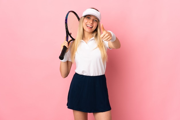 Joven mujer rubia aislada en rosa jugando al tenis y con el pulgar hacia arriba