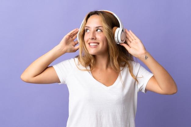 Joven mujer rubia aislada sobre fondo púrpura en pijama y sosteniendo una almohada y escuchando música