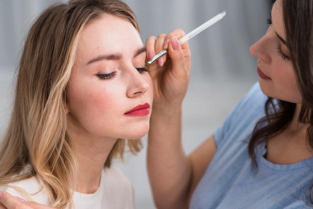 Joven mujer rubia y artista haciendo maquillaje de ojos