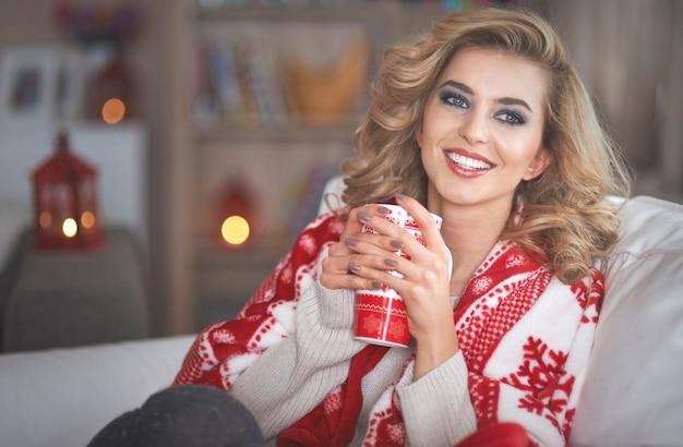 Joven mujer rubia bebiendo chocolate caliente