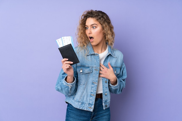 Joven mujer rubia con cabello rizado aislado en pared púrpura en vacaciones con boletos de avión y sorprendido
