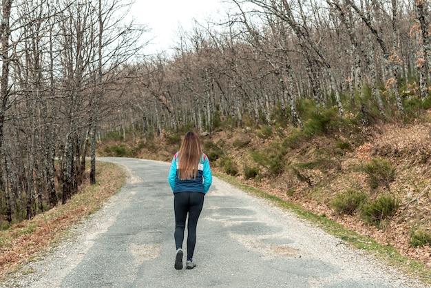 Joven mujer rubia caminando por una carretera de montaña.