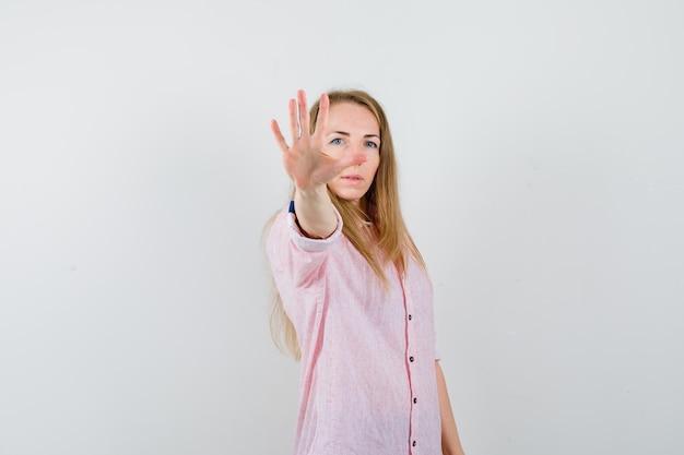 Joven mujer rubia en una camisa rosa casual que muestra la señal de stop