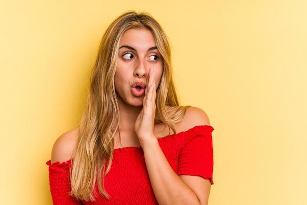 Joven mujer rubia caucásica aislada sobre fondo amarillo está diciendo una noticia secreta de frenado en caliente y mirando a un lado