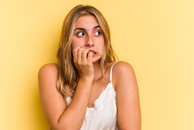 Joven mujer rubia caucásica aislada sobre fondo amarillo mordiéndose las uñas, nerviosa y muy ansiosa.