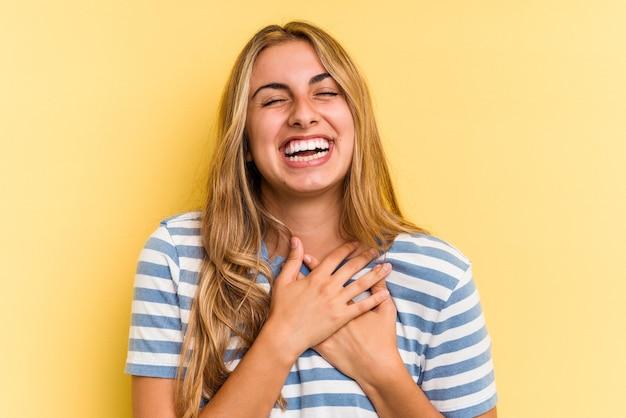 Joven mujer rubia caucásica aislada sobre fondo amarillo riendo manteniendo las manos en el corazón, concepto de felicidad.