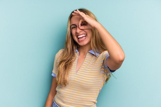 Joven mujer rubia caucásica aislada sobre fondo azul emocionado manteniendo el gesto ok en el ojo.