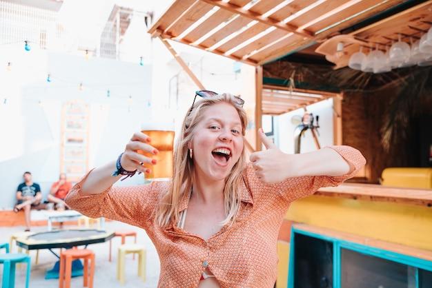 Joven mujer rubia caucásica feliz para una celebración y bebiendo un vaso de cerveza