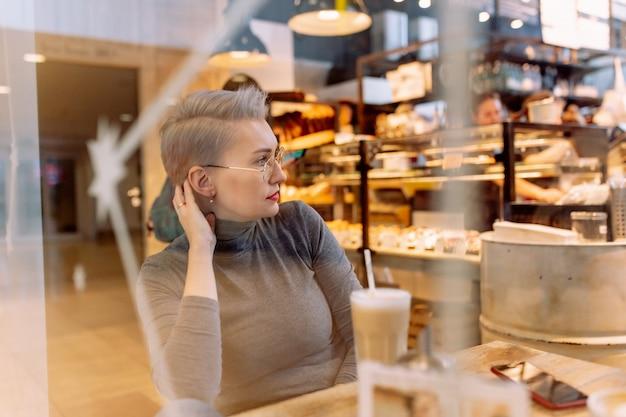 Joven mujer rubia caucásica grabando mensajes de audio con smartphone sentado en el café