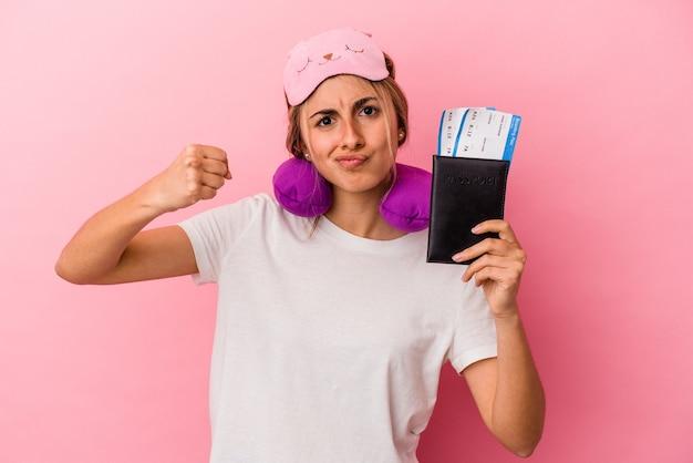 Joven mujer rubia caucásica sosteniendo un pasaporte y boletos para viajar aislado sobre fondo rosa mostrando el puño a la cámara, expresión facial agresiva.