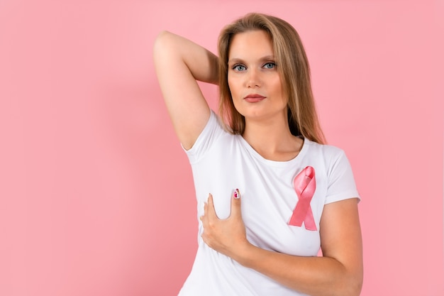Joven mujer rubia con cinta rosa en camiseta compruebe su pecho con la mano en rosa