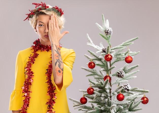 Joven mujer rubia con corona de navidad y guirnalda de oropel alrededor del cuello de pie cerca del árbol de navidad decorado mirando a la cámara que cubre la mitad de la cara con la mano aislada sobre fondo blanco