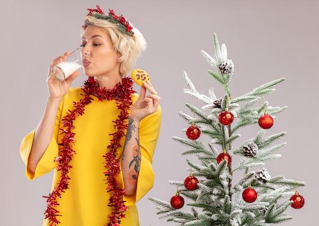 Joven mujer rubia con corona de navidad y guirnalda de oropel alrededor del cuello de pie cerca del árbol de navidad decorado con vaso de leche y galletas bebiendo leche aislado sobre fondo blanco