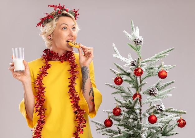 Joven mujer rubia con corona de navidad y guirnalda de oropel alrededor del cuello de pie cerca del árbol de navidad decorado con vaso de leche mordiendo galletas mirando hacia arriba aislado sobre fondo blanco.