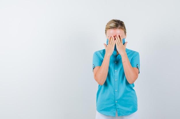 Joven mujer rubia cubriendo los ojos con las manos en ropa casual, máscara y mirando pensativo