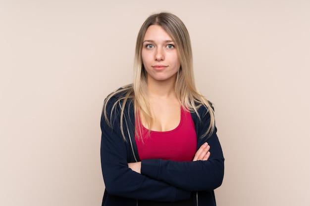 Joven mujer rubia deporte con los brazos cruzados