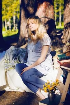 Joven mujer rubia embarazada está durmiendo en una cama en la naturaleza. el concepto de un buen sueño.