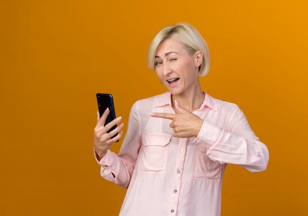 Joven mujer rubia eslava sosteniendo y apunta al teléfono