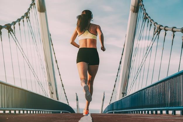Joven mujer rubia en forma corriendo en el puente