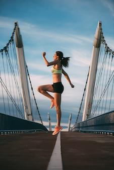 Joven mujer rubia en forma saltando en el puente