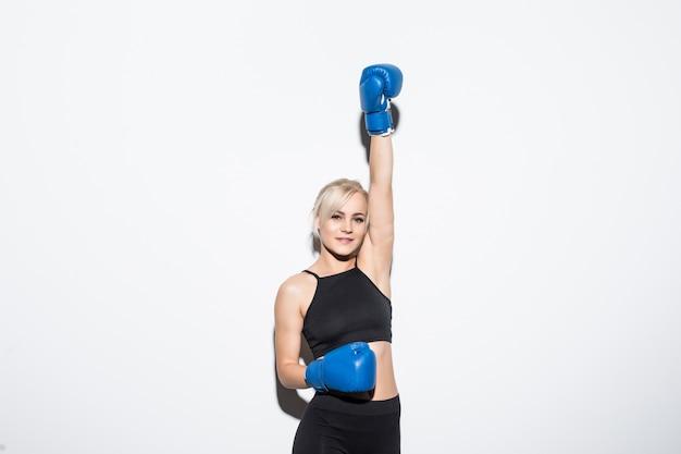 Joven mujer rubia con guantes de boxeo azules en la mano blanca de la victoria