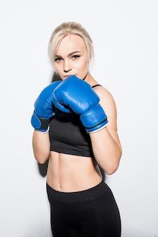 Joven mujer rubia con guantes de boxeo azules preparados para luchar en blanco