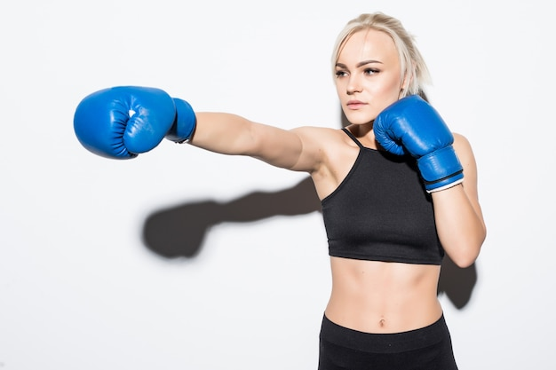 Joven mujer rubia con guantes de boxeo azules sobre blanco